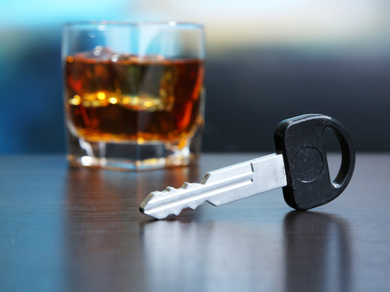 a glass of alcohol with a car key next to it